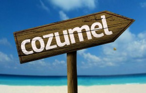 Cozumel wooden sign with a beach on background